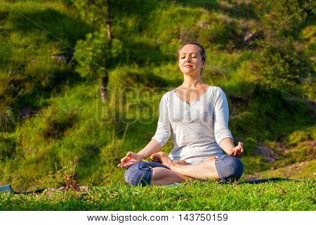 Young sporty fit woman doing yoga outdoors - meditating and relaxing in Padmasana Lotus Pose) with chin mudra on green grass in forest