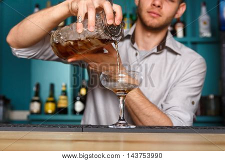 Barman's hands in bar interior mixing alcohol cocktail. Professional bartender at work in bar pouring drink with ice into glass