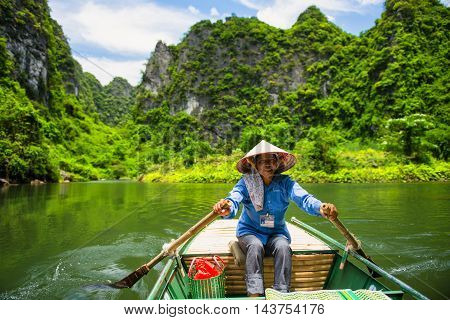 Ninh Binh, Vietnam - 02 June, 2013: The woman drive the boat in the river