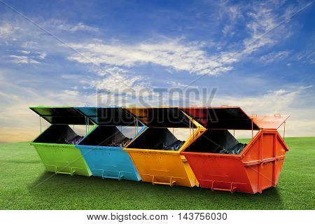 Colorful Industrial Waste Bin (dumpster) for municipal waste or industrial waste on green grass and blue sky backgroundwith ecology concept
