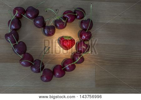 Several cherries in heart shape with one strawberry are on the light wooden background