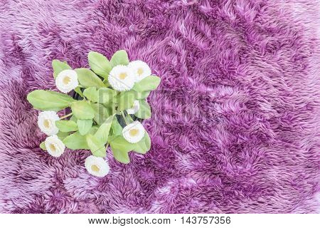 Closeup artificial plant with white flower on purple pot on purple carpet textured background in top view
