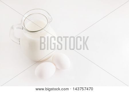 Jug With Milk And Two Eggs On White Background