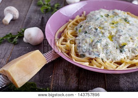 Pasta sphaghetti with mushroom sauce on wood background with forks and cheese near it