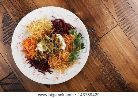 Chafan (Azerbaijan kitchen), mix from potato, carrot, beet, greens on white plate. wooden background