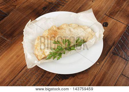 cheburek with meat on white plate. chiburekki - traditional asia kitchen. wooden background