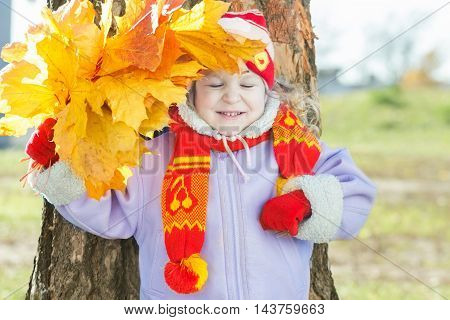 Laughing little girl is holding yellow with orange autumn leaves bunch in hand outdoor portrait