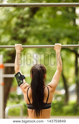 Young brunette doing chin-ups on the gym bar, portrait of woman in the back