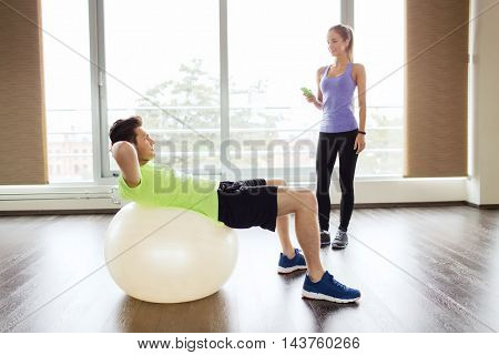 sport, fitness, lifestyle and people concept - smiling man and woman flexing muscles with exercise ball in gym