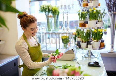 people, business, sale and floristry concept - happy smiling florist woman making tulip bunch at flower shop