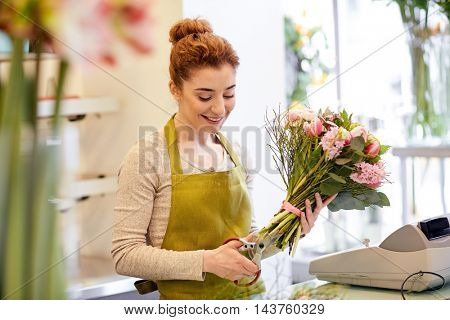 people, business, sale and floristry concept - happy smiling florist woman making bunch and cropping stems by scissors at flower shop