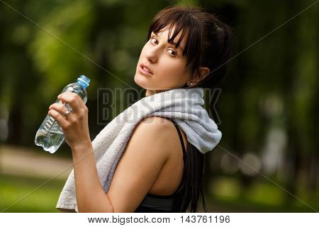 Young sporty woman with towel on shoulders holding bottle of water, portrait outdoors, model looking at camera