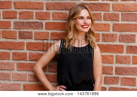 Fashion portrait of beautiful blonde woman with red lipstick wearing black blouse against brick wall outdoors