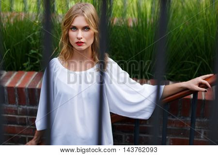 Outdoors portrait of young attractive blonde with curly hair in white blouse through metal bars
