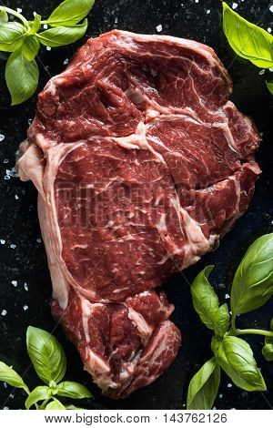 Fresh steak served with spices tomatoes and leafs of basil on marble background. Uncooked beefsteak cooking on a kitchen. Delicious spicy juicy meat with copy space closeup.