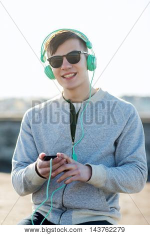 technology, lifestyle and people concept - smiling young man or teenage boy in headphones with smartphone listening to music outdoors