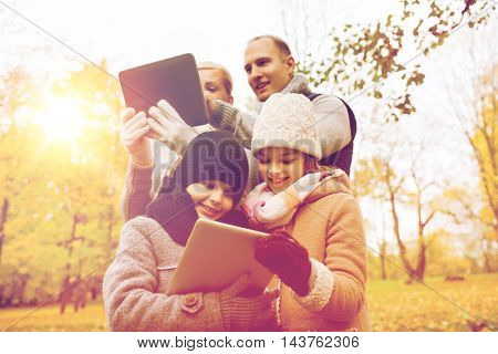 family, childhood, season, technology and people concept - happy family with tablet pc computers in autumn park