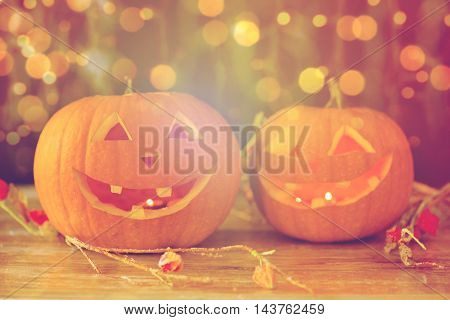 holidays, halloween and decoration concept - close up of carved pumpkins with smiley faces on table over lights