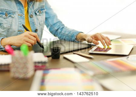 Designer workplace. Woman using tablet