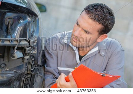 Mechanic assessing car