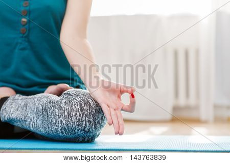 Young woman sitting in lotus position in gym and hands gesturing zen