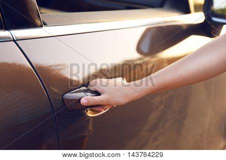 Woman hand opening car door, close up
