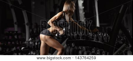 Fitness woman in the gym. Muscular blonde fitness woman doing exercises in the gym
