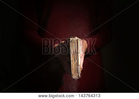 Woman holding old book on dark background