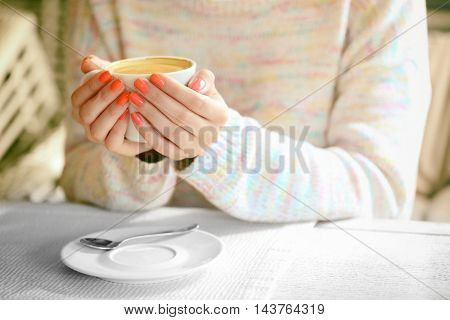 Woman hands holding cup of coffee in cafe