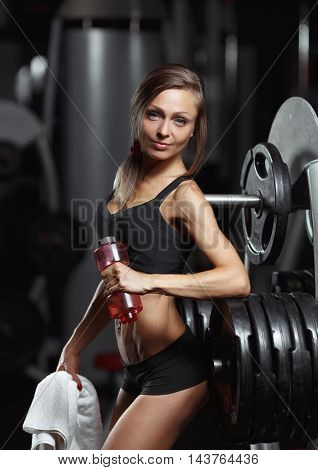 Beautiful fitness woman resting after a workout and keep a bottle of water and towel. Fitness woman resting in the gym.