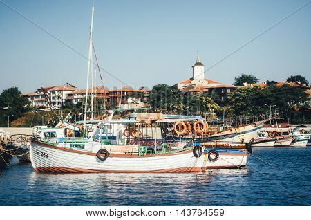 NESSEBAR BULGARIA AUGUST 31 2015: Old wooden fishing boat in port against the backdrop of the Church Of The Holy Virgin in ancient Nessebar.