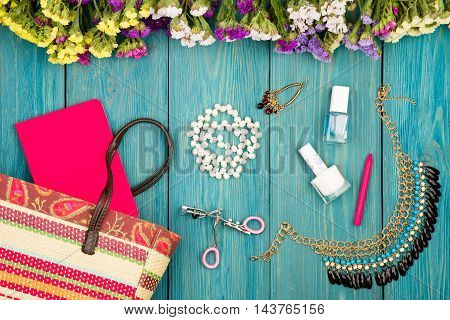 Straw Bag, Colorful Flowers, Cosmetics Makeup, Notepad, Bijou And Essentials On Blue Wooden Backgrou