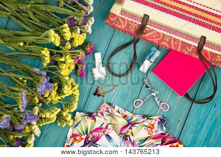 Straw Bag, Dress, Colorful Flowers, Cosmetics Makeup, Notepad, Bijou And Essentials On Blue Wooden B