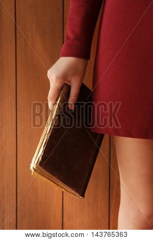 Woman holding old book on wooden background