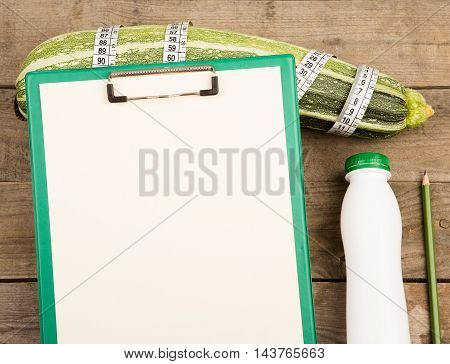 Marrow Squash, Measure Tape, Blank Clipboard And Bottle Of Water On Brown Wooden Table