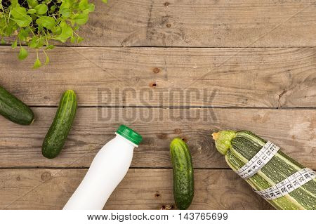 Marrow Squash, Measure Tape, Bottle Of Water And Cucumbers On Brown Wooden Table