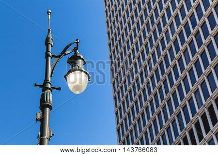 Old design of a street lamp which is still on in spite of the blue sky day. Detail of a skyscraper. Downtown Detroit Michigan USA.