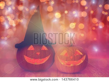 holidays, halloween and decoration concept - close up of carved pumpkins with smiley faces and witch hat on table over lights