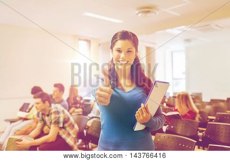 education, high school, gesture and people concept - group of smiling students with notepads showing thumbs up in lecture hall