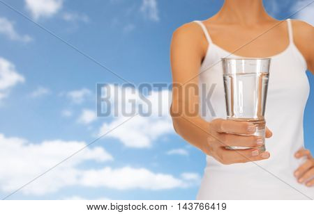 close up of woman hand holding glass of water over blue sky and clouds background