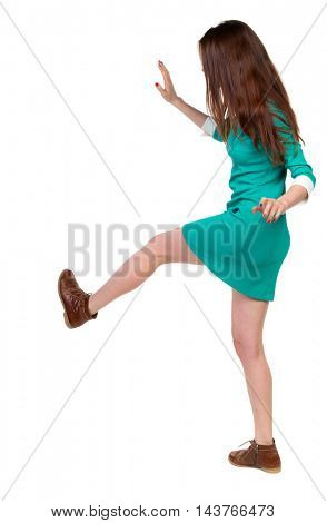 skinny woman funny fights waving his arms and legs. Isolated over white background. Long-haired brunette in a green dress kicks.