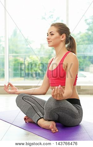 Girl practicing advanced yoga on light background