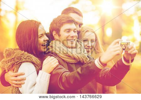 summer, holidays, vacation, travel, tourism, happy people concept - group of friends or couples having fun with photo camera in autumn park