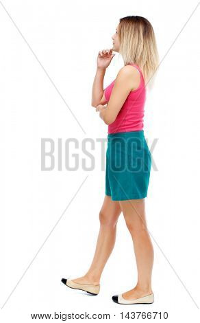 back view of walking  woman. beautiful girl in motion.  backside view of person.  Rear view people collection. Isolated over white background. Blonde in a red sweater and green skirt is rubbing his
