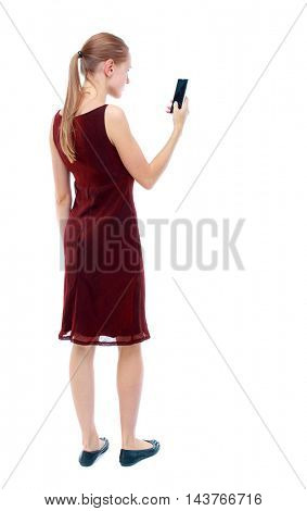 back view of standing young beautiful  woman  using a mobile phone. girl  watching. Rear view people collection.  backside view of person.  Isolated over white background. The girl in the maroon