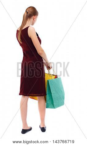 back view of woman with shopping bags. backside view of person.  Rear view people collection. Isolated over white background. Slim blonde in a burgundy dress holding colorful bags in hand.
