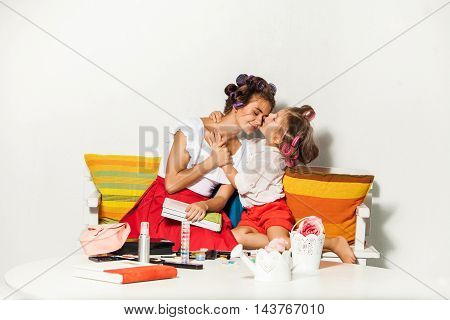 Little girl playing with her mother on white