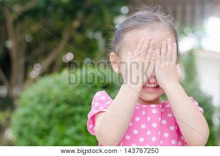 Little asian girl enjoy playing hide and seek outdoor