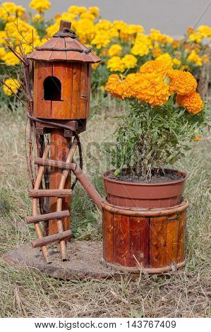 decorative wooden birdhouse next to the flowers in the garden
