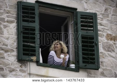 Beautiful blonde woman is looking into the distance with cup of coffee in her hands
